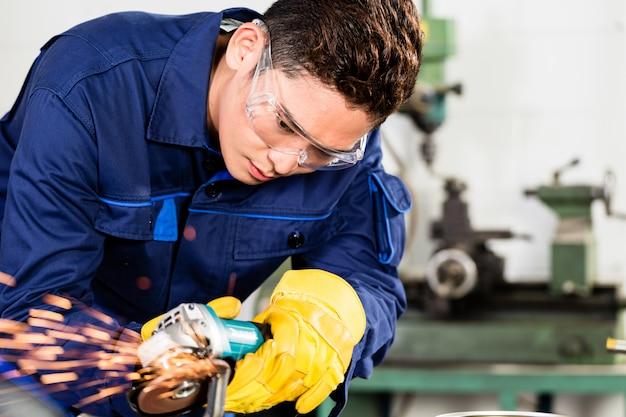 Trabajador asiático moliendo metal en planta de fabricación