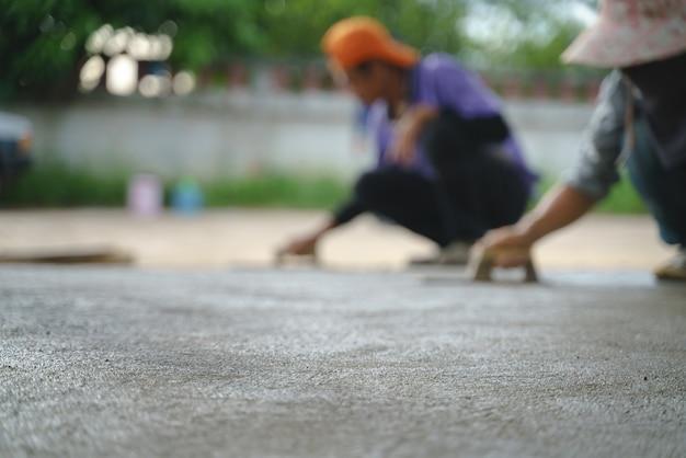 Trabajador asiático trabajando con piso de cemento de concreto.