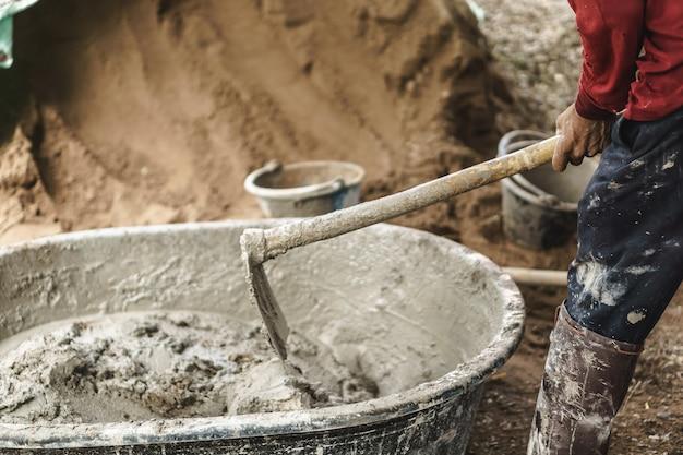 Trabajador asiático usando azada para mezclar el poder del cemento con arena