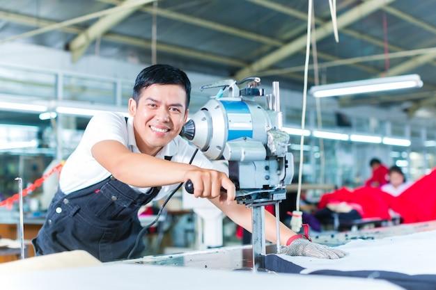 Trabajador asiático utilizando una máquina en una fábrica.
