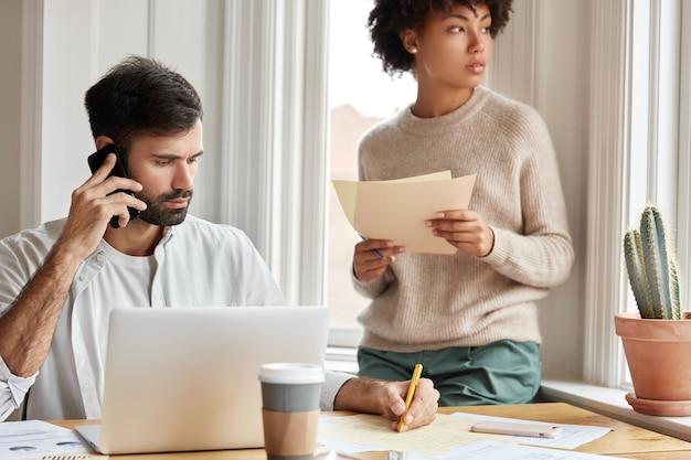 El trabajador autónomo que trabaja duro utiliza tecnologías modernas, resuelve problemas a distancia, escribe información en documentos