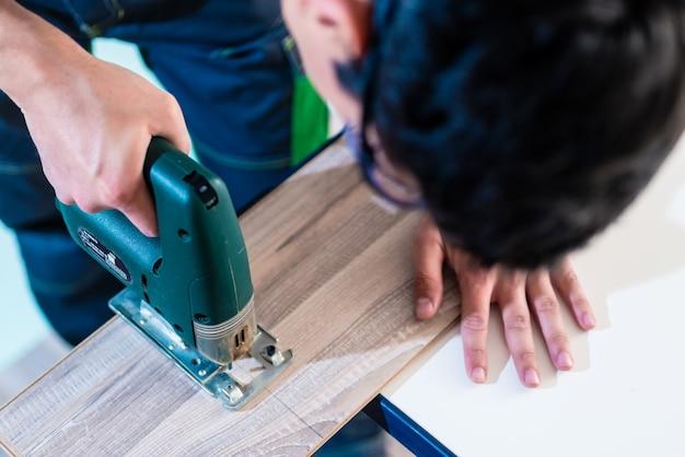Trabajador de bricolaje cortando panel de madera con sierra de calar