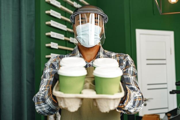 Trabajador de la cafetería con máscara médica mientras está de pie en el mostrador de la cafetería