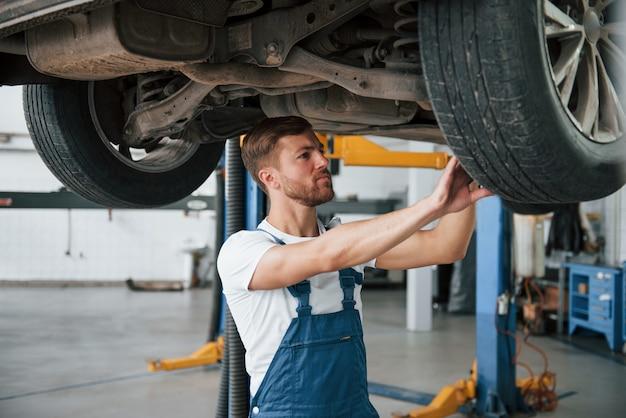 Un trabajador calificado. empleado con uniforme de color azul tiene trabajo en el salón del automóvil