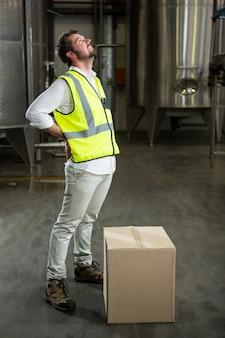 Trabajador cansado de pie en el almacén