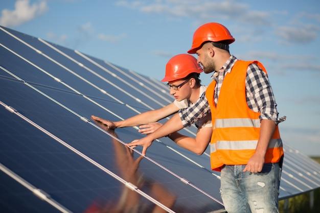 Trabajador y capataz manteniendo panel de energía solar.