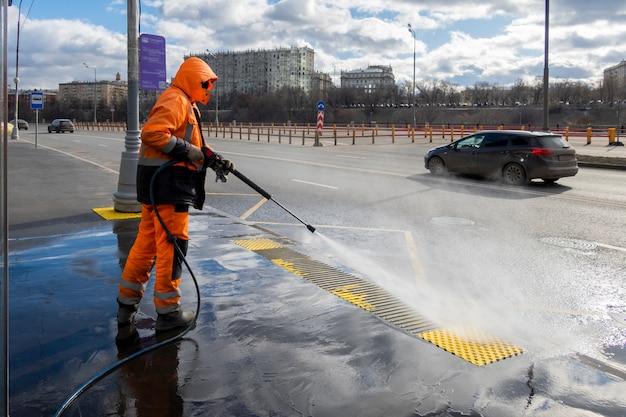 Trabajador de la carretera de limpieza de calles de la ciudad con lavadora de alta presión, moscú, rusia