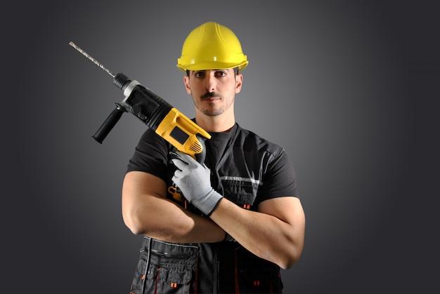 Trabajador con casco amarillo, taladro y martillo.