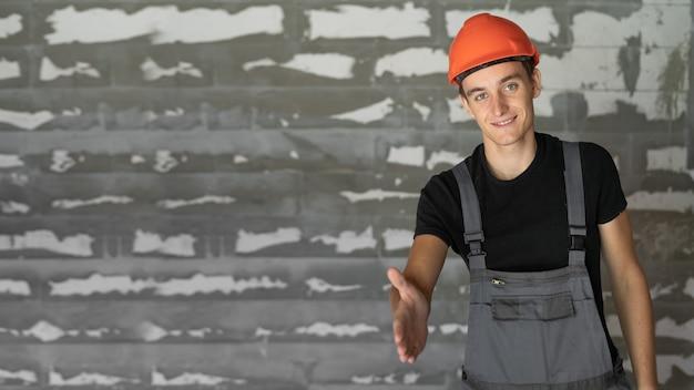 Trabajador con casco naranja cerca de un muro de piedras. extiende su mano para hacer un apretón de manos.