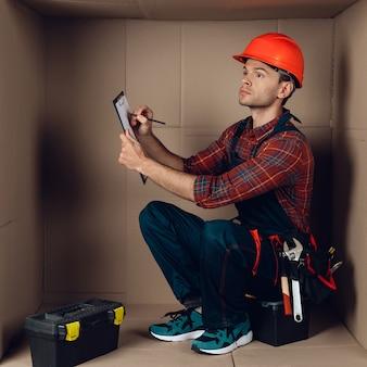 Trabajador en casco naranja sentado en caja de cartón.