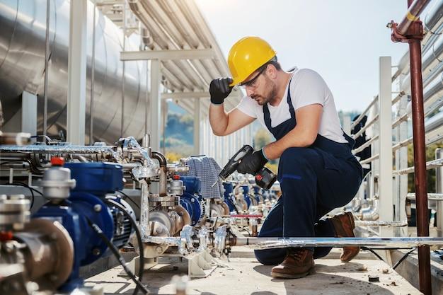 Trabajador caucásico guapo en general y casco en cabeza agachado y usando taladro mientras se agacha. industria del aceite.