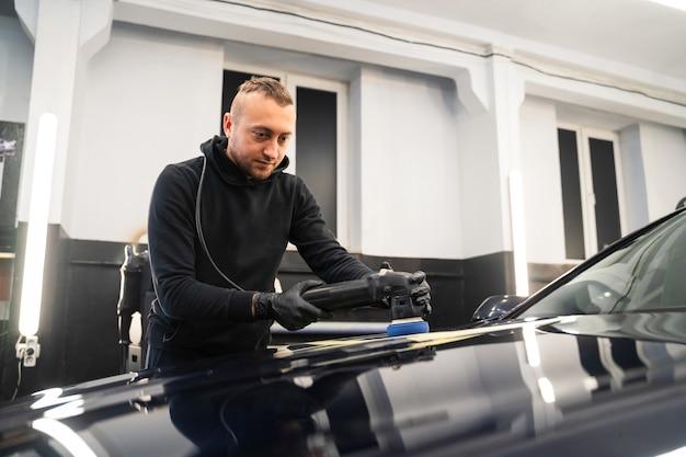 Trabajador del centro de detalle pule la carrocería del automóvil con una pulidora