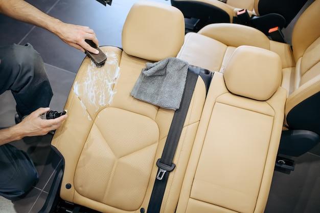 Trabajador con cepillo y toallitas en aerosol quitó el asiento del automóvil, vista superior, limpieza en seco y detalles.