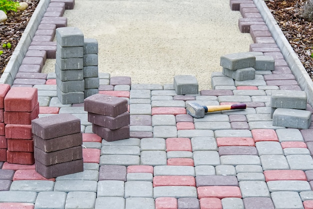 Trabajador colocando adoquines. pavimento de piedra, trabajador de la construcción colocando rocas de adoquines en la arena.