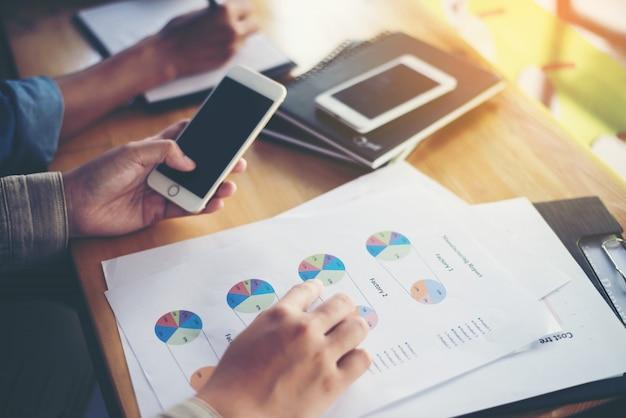 Trabajador comparando gráficos en papel con su móvil