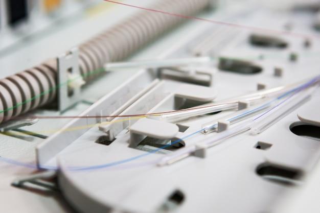Trabajador comunica cable de fibra óptica en caja opto. instalando nuevos equipos de red