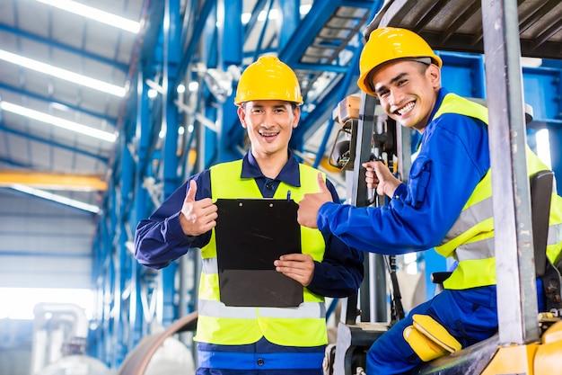 Trabajador y conductor de carretilla elevadora en fábrica industrial.