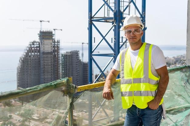 Trabajador de la construcción al aire libre de pie a gran altura