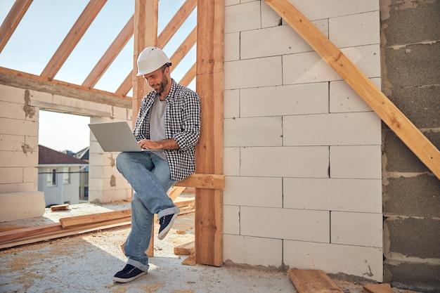 Trabajador de la construcción ambicioso en un casco sosteniendo su computadora portátil