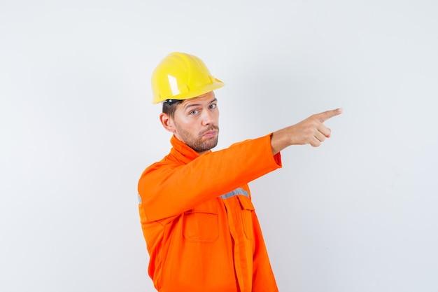 Trabajador de la construcción apuntando hacia afuera en uniforme, casco y mirando confiado. vista frontal.