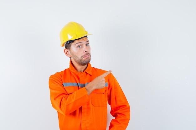 Trabajador de la construcción apuntando hacia afuera en uniforme, casco y mirando vacilante, vista frontal.