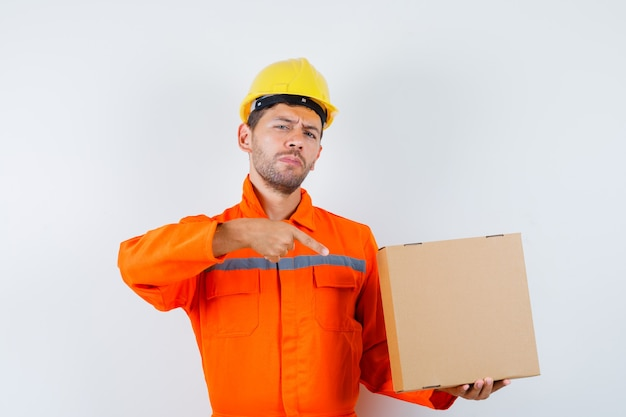 Trabajador de la construcción apuntando a la caja de cartón en uniforme, vista frontal del casco.