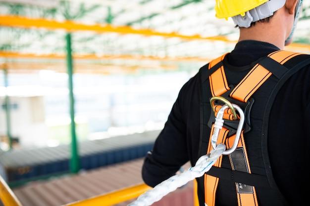 Trabajador de la construcción con arnés de seguridad y línea de seguridad trabajando en la construcción.