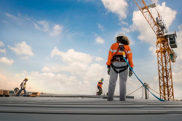 Trabajador de la construcción con arnés de seguridad y línea de seguridad trabajando en un roo de la industria del metal
