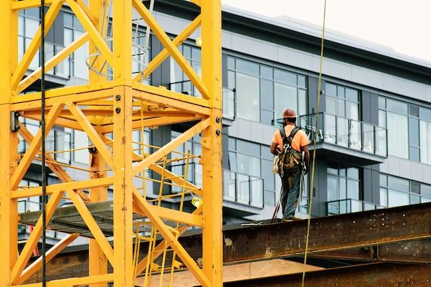 Trabajador de la construcción con arneses de seguridad y línea de seguridad