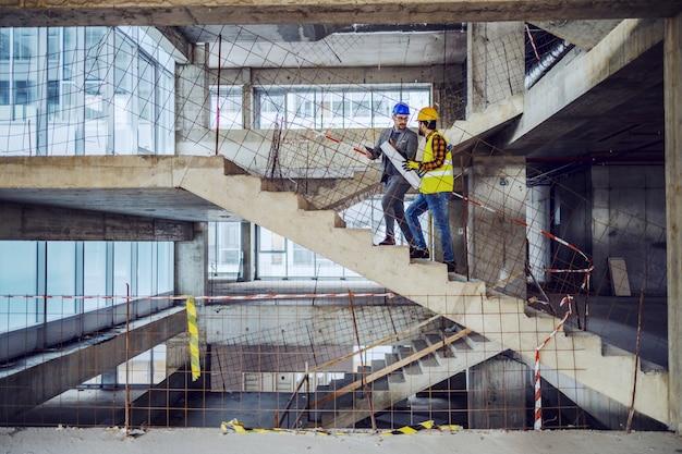 Trabajador de la construcción y arquitecto principal subiendo las escaleras y hablando sobre el progreso en la construcción del nuevo edificio.
