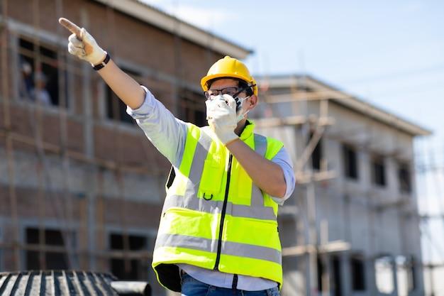 Trabajador de la construcción asiática hablando por un walkie talkie en el sitio de construcción. usar mascarilla quirúrgica durante el coronavirus y el brote de gripe