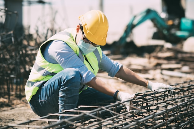 Trabajador de la construcción asiática en obra. fabricación de barra de refuerzo de acero. usar mascarilla quirúrgica durante el coronavirus y el brote de gripe
