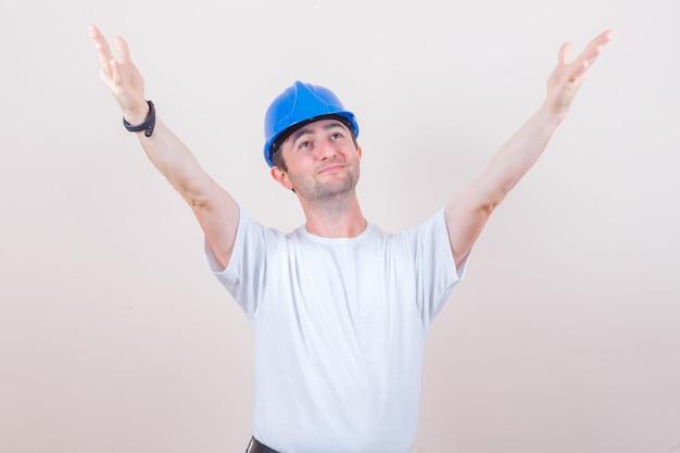 Trabajador de la construcción en camiseta, casco abriendo los brazos para abrazar y lucir alegre