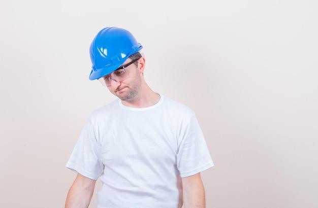 Trabajador de la construcción en camiseta, casco mirando hacia abajo y mirando desesperado
