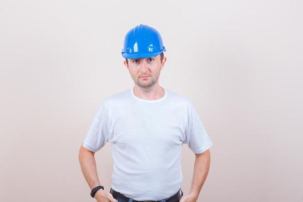 Trabajador de la construcción en camiseta, casco mirando a cámara y mirando sensato
