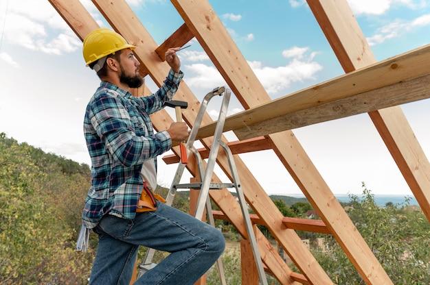 Trabajador de la construcción con casco y martillo construyendo el techo de la casa