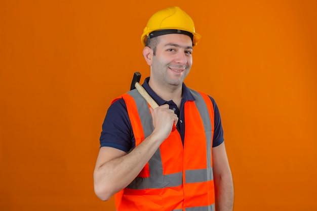 Trabajador de la construcción con chaleco y casco de seguridad amarillo con martillo con una sonrisa en la cara aislada en naranja