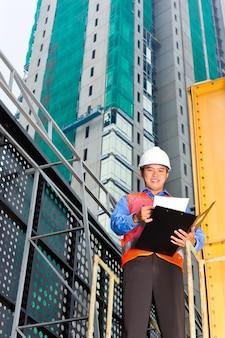 Trabajador de la construcción chino o supervisor o arquitecto con portapapeles en una obra en construcción en asia