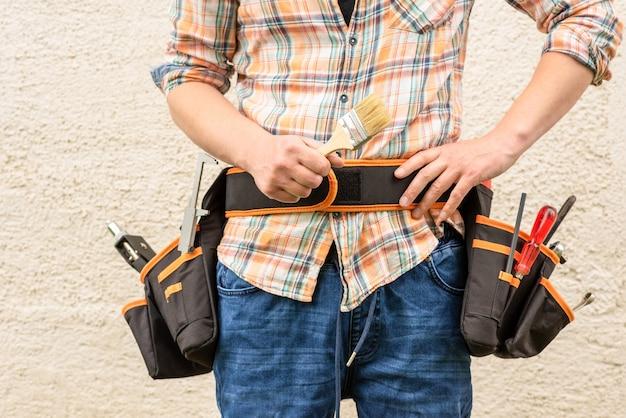 Un trabajador de la construcción en un cinturón de construcción con herramientas sostiene un pincel
