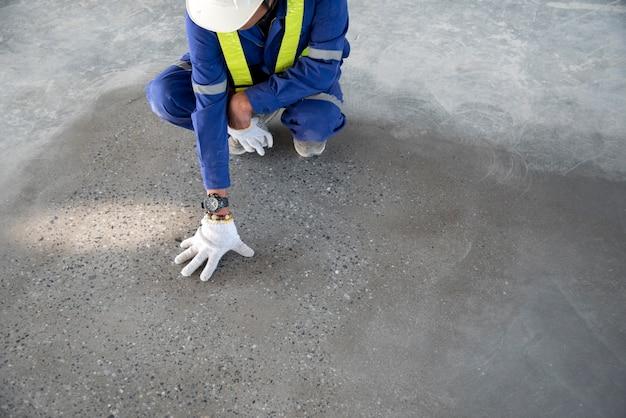 Un trabajador de la construcción compruebe el piso de epoxy de la calidad en la fábrica japón del almacén de la construcción si