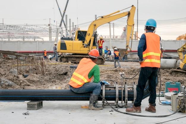 Trabajador de la construcción conecta la tubería de hdpe en el sitio de construcción