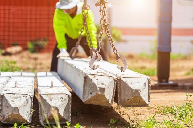 Trabajador de la construcción descargando estaca de concreto del camión
