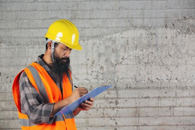 Trabajador de la construcción con documento, plan de trabajo para el interior del sitio de construcción del edificio.