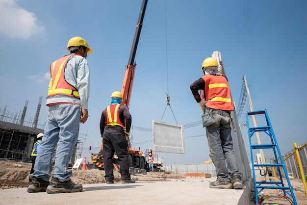 Trabajador de la construcción e ingeniero mirando grúa móvil levante muro de hormigón prefabricado