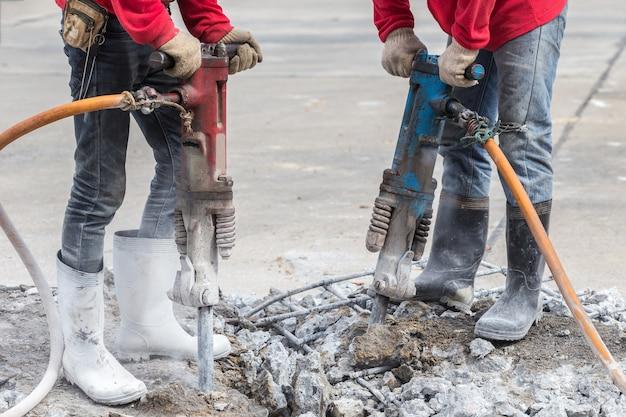 Trabajador de la construcción elimina el exceso de hormigón con la máquina de perforación en el sitio de construcción