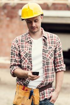 Trabajador de la construcción enviando mensajes de texto en el teléfono móvil