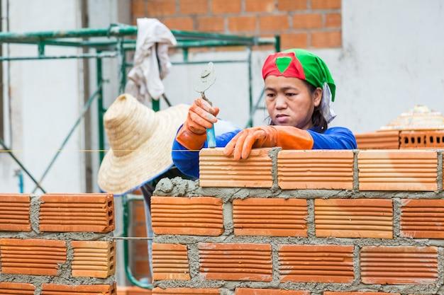 Trabajador de la construcción femenina apila ladrillos de terracota para hacer la pared en un sitio de construcción
