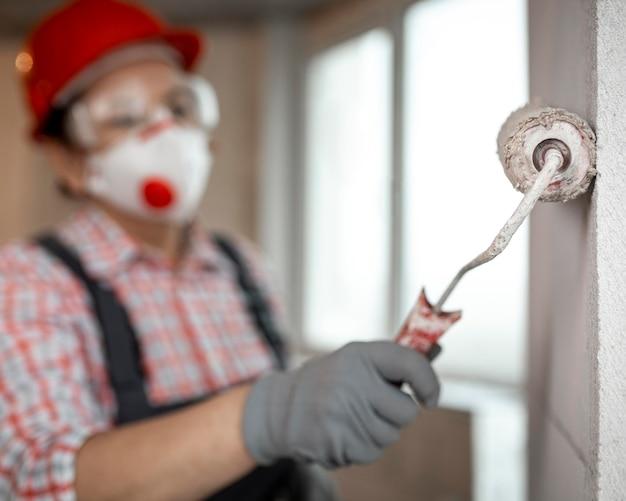 Trabajador de la construcción femenina con casco y rodillo de pintura