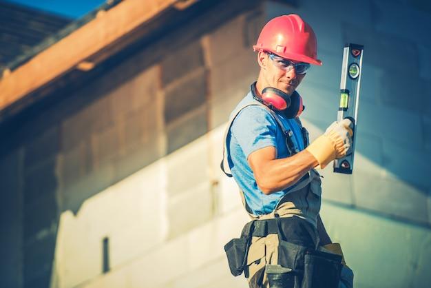 Trabajador de la construcción con herramienta de nivel y el sitio de construcción.