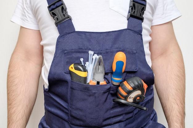 Trabajador de la construcción con herramientas en el bolsillo.